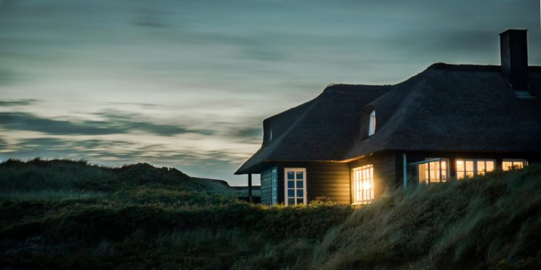 House at night with light shining.