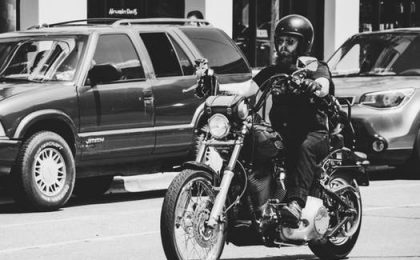 man with beard and helmet on a motorcycle