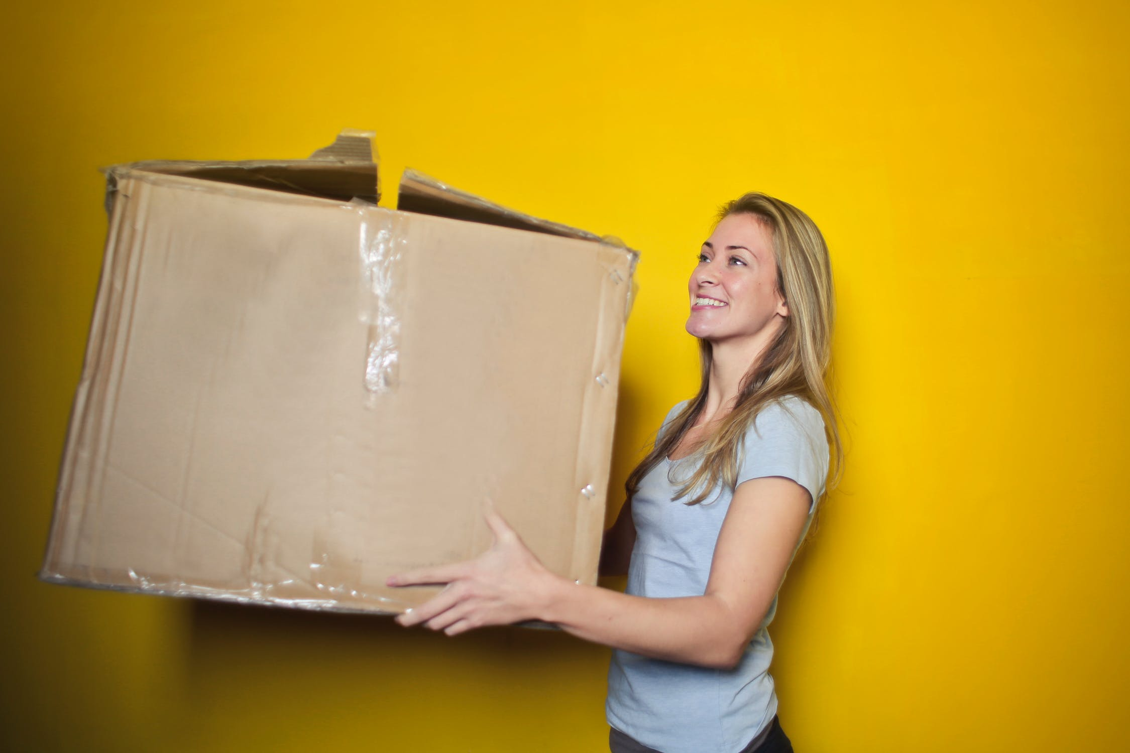 Woman holding moving box.