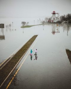 Children walking in flood waters near lighthouse.