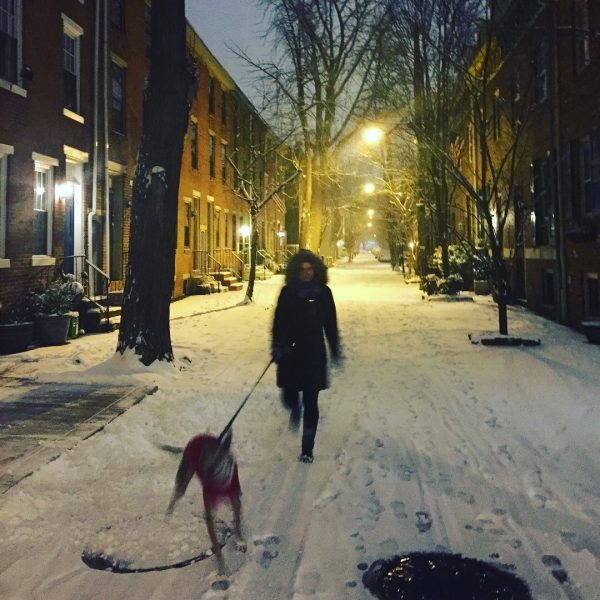 Woman walking dog in snow.