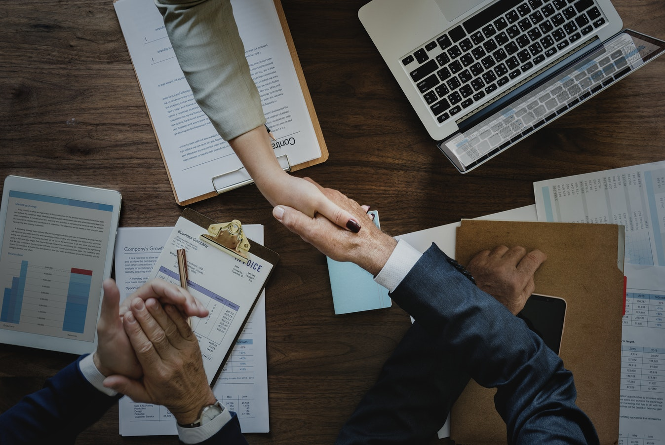 Two people shaking hands over a business deal.
