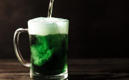 Person pouring green beer.