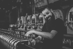 Bartender smiling while pouring beer.