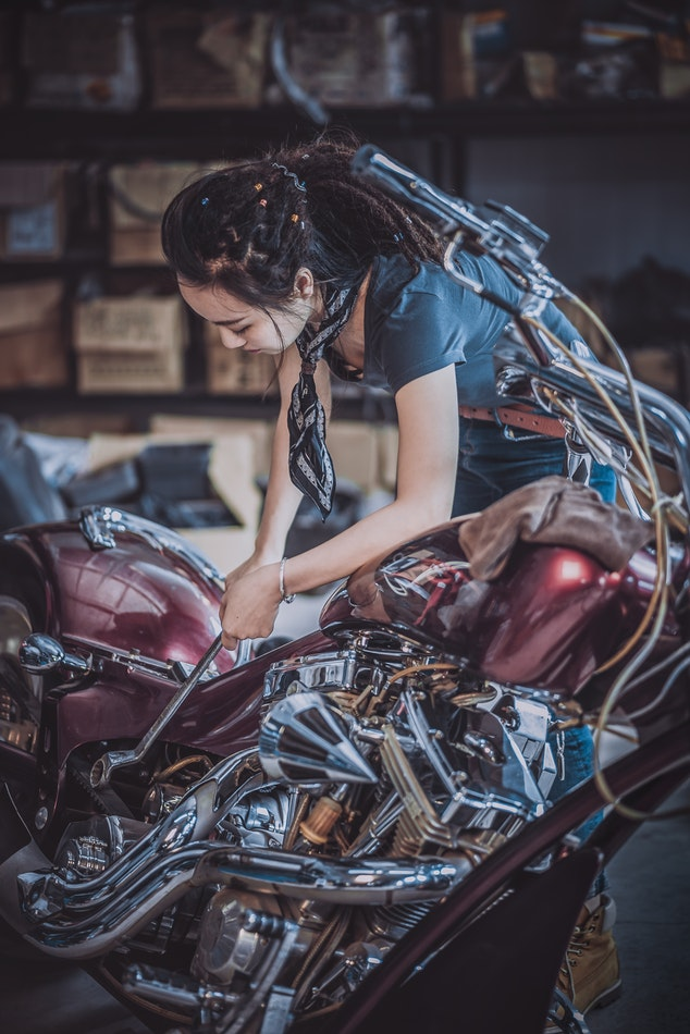 Woman working on a motorcycle.
