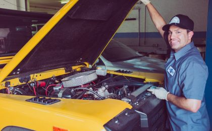 Mechanic standing in front of car.