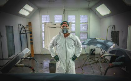 Man standing in painting gear with auto parts.