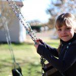 Little girl on swing set.