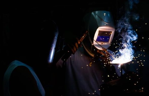 Man welding wearing garage safety visor.