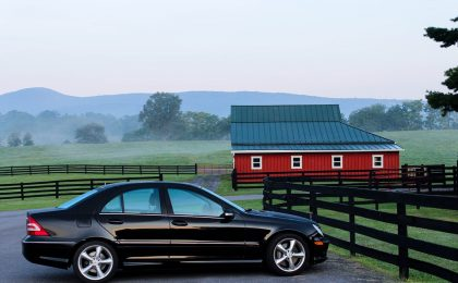 Black sedan with commercial auto insurance in front of a red barn.