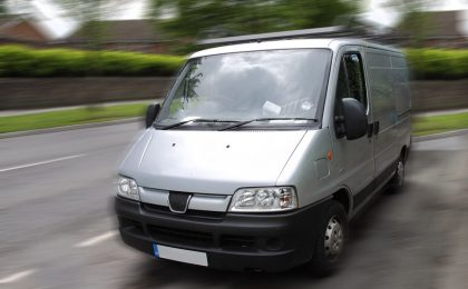 Silver van with commercial auto insurance driving down a road.