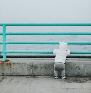 Baby thinking about communication while looking at the water.