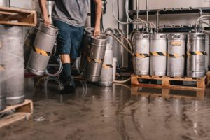 Man dragging kegs over a wet ground and risking a General Liability claim.