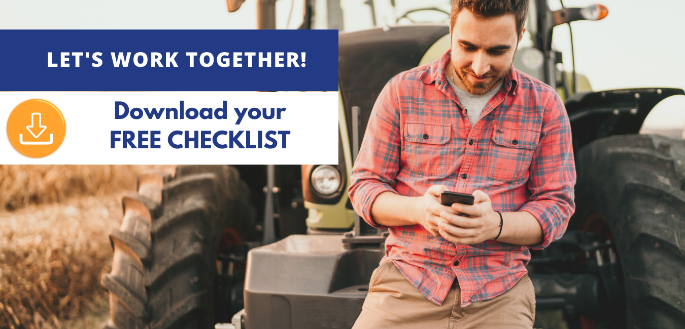 Farmer leaning against a tractor while downloading a free farm checklist on his phone.